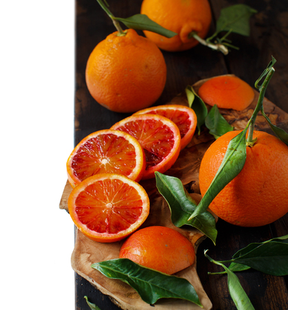Fresh  oranges with leaves on an old table isolated on white