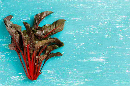 Fresh red chard from a farmers market top view on a turquoise blue background