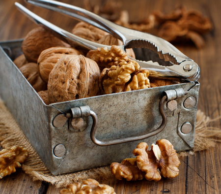 Fresh walnuts in a box on a  wooden table close up