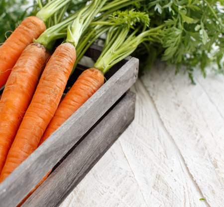 Fresh raw carrots with leaves in a box on a wooden table