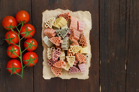 Tricolor fir tree shaped pasta and cherry tomatoes on wood Archivio Fotografico