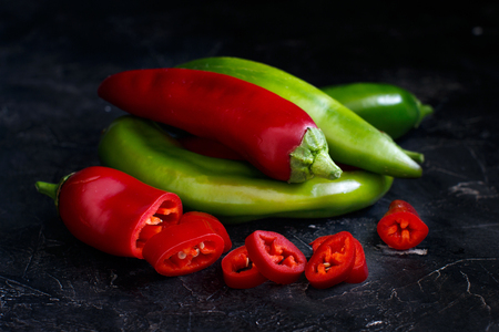 Red and green sweet peppers on dark background