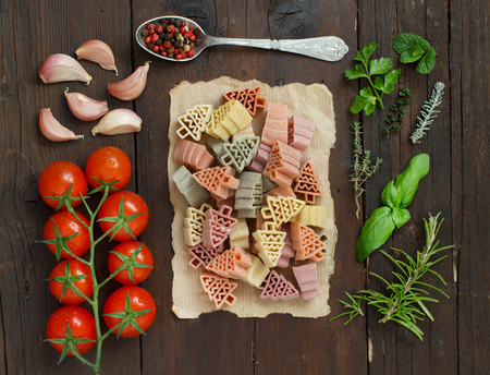 Tricolor fir tree shaped pasta, vegetables and herbs on wood Archivio Fotografico