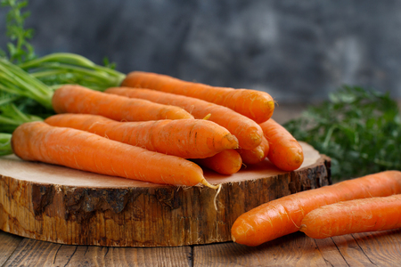 Fresh raw carrots with leaves on a wooden table Archivio Fotografico