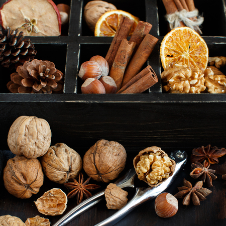 A box full of spices and nuts on a wooden table top view Archivio Fotografico