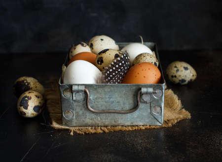 Ð¡hicken and quail eggs in a box on a dark background Archivio Fotografico
