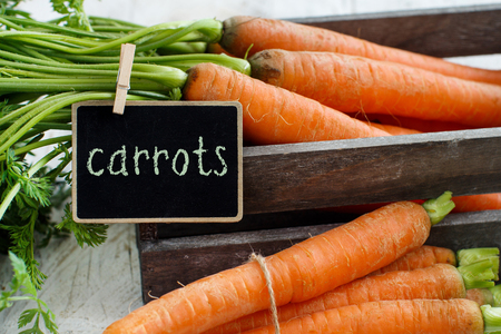 Fresh raw carrots with leaves in a box with a small chalkboard on a wooden table