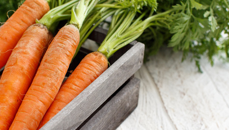 Fresh raw carrots from a farmers market on a wooden table