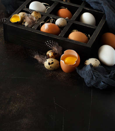 �¡hicken and quail eggs in a box on a dark background