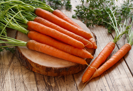 Fresh raw carrots with leaves on a white wooden table