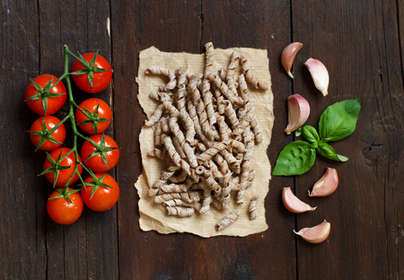 Whole wheat pasta, tomatoes, basil and garlic on a wooden background