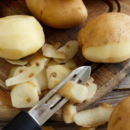 Raw potatoes with a vegetable peeler top view