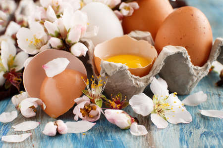 Ð¡hicken eggs and almond flowers on  a blue wooden background