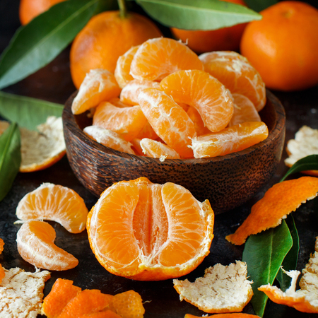 Mandarins with leaves in a bowl on a dark background