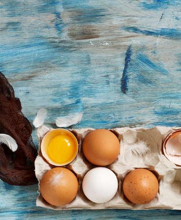 Ð¡hicken eggs in a box on  a blue wooden background Archivio Fotografico