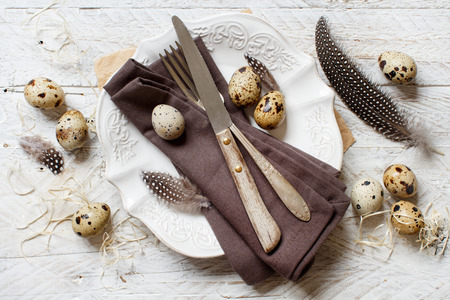 Easter table setting with quail eggs and feathers