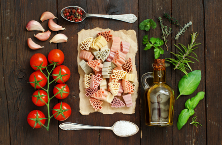 Tricolor pasta, vegetables and herbs on a wooden background