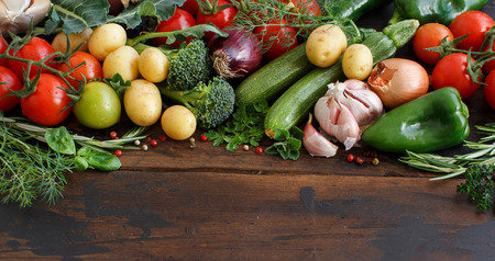 Fresh raw vegetables and herbs on a wooden background Stock Photo