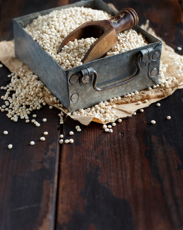 Raw White Sorghum grain in a metal box on a dark wooden table Stock Photo