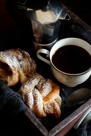 Cup of coffee with croissant on a dark background Stock Photo