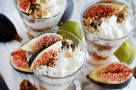 Greek yogurt with figs and granola in a glass close up