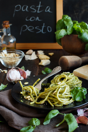 Spaghetti pasta with pesto sauce, basil, pine nuts and parmesan close up
