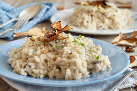 Risotto with porcini mushrooms on a blue plate on a wooden table