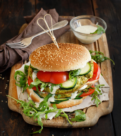 Healthy vegetarian burger with broccoli burger, arugula, zucchini and tomatoes