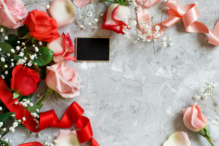 Red roses flowers, petals and small chalkboard on a grey background