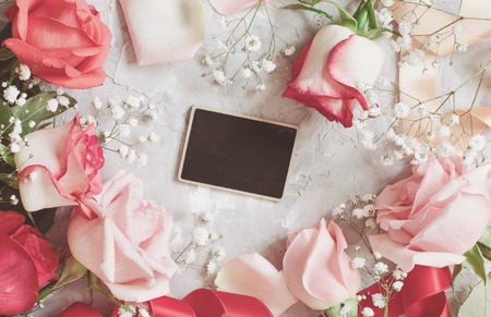 Red roses and small white flowers with a chalkboard on a grey background