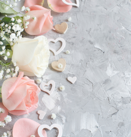 Pink and cream roses with hearts on a grey background