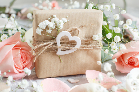 Gift box with roses and small white flowers  on a grey background Imagens