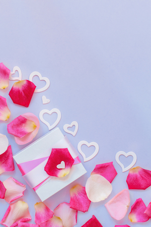Spring composition with gift box, petals and hearts on a pastel  background