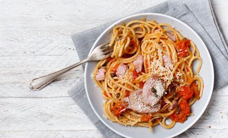 Spaghetti with chunks of fresh tuna, tomato and capers close up