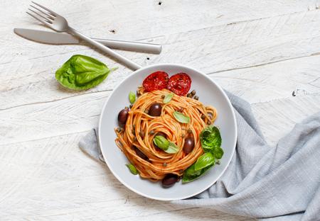 Pasta alla puttanesca - Spaghetti with tomato sauce olives and capers Foto de archivo