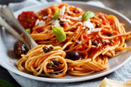 Pasta alla puttanesca - Spaghetti met tomatensaus, olijven en kappertjes Stockfoto