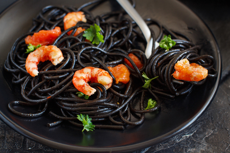 Squid ink black spaghetti with prawns and tomatoes close up