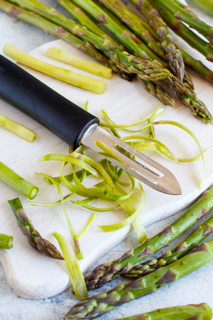 Fresh asparagus with a peeler on a white table close up