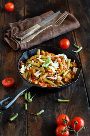 French beans with tomato stew close up on a dark table Stock Photo