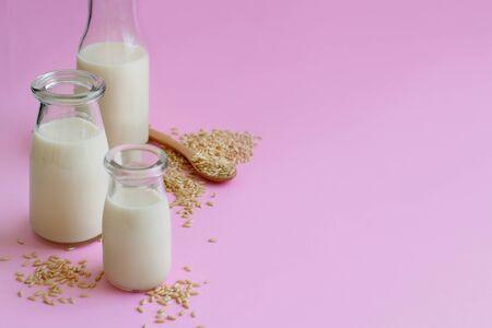 Vegan rice milk, non dairy alternative milk in a bottle on a pink background