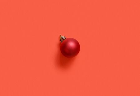 Red Christmas bauble on a red background top view 스톡 콘텐츠