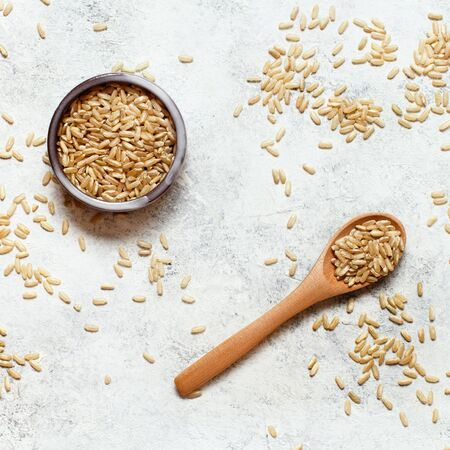 Brown rice in a wooden bowl with a  spoon top view Imagens