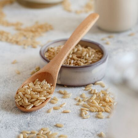 Brown rice in a wooden spoon with rice milk close up Imagens