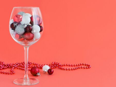 Christmas baubles in a wine glass on a coral red background close up Stock Photo