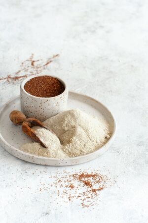 Teff flour on a plate and teff grain in a bowl close up