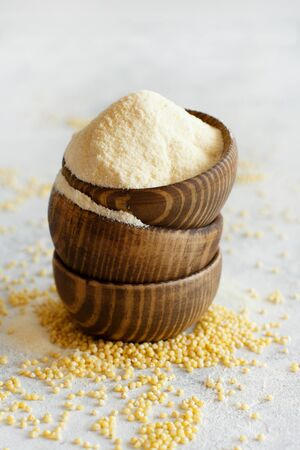 Hulled millet flour in wooden bowls and grain close up