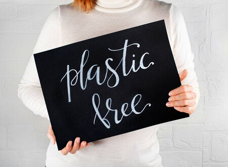 Woman keeping a small chalkboard with Plastic Free lettering close up