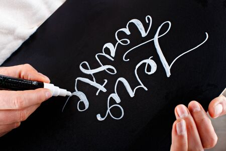 Woman writing on a small chalkboard zero waste lettering close up Stock Photo