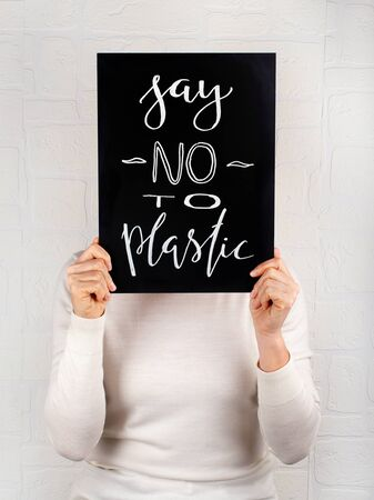 Woman keeping a small chalkboard with  SAY NO TO PLASTIC lettering close up