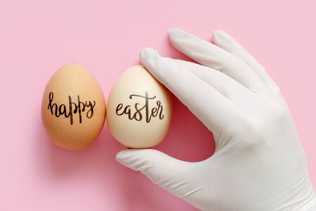 Hand in glove keeping eggs with inscription HAPPY EASTER over light pink background top view Imagens